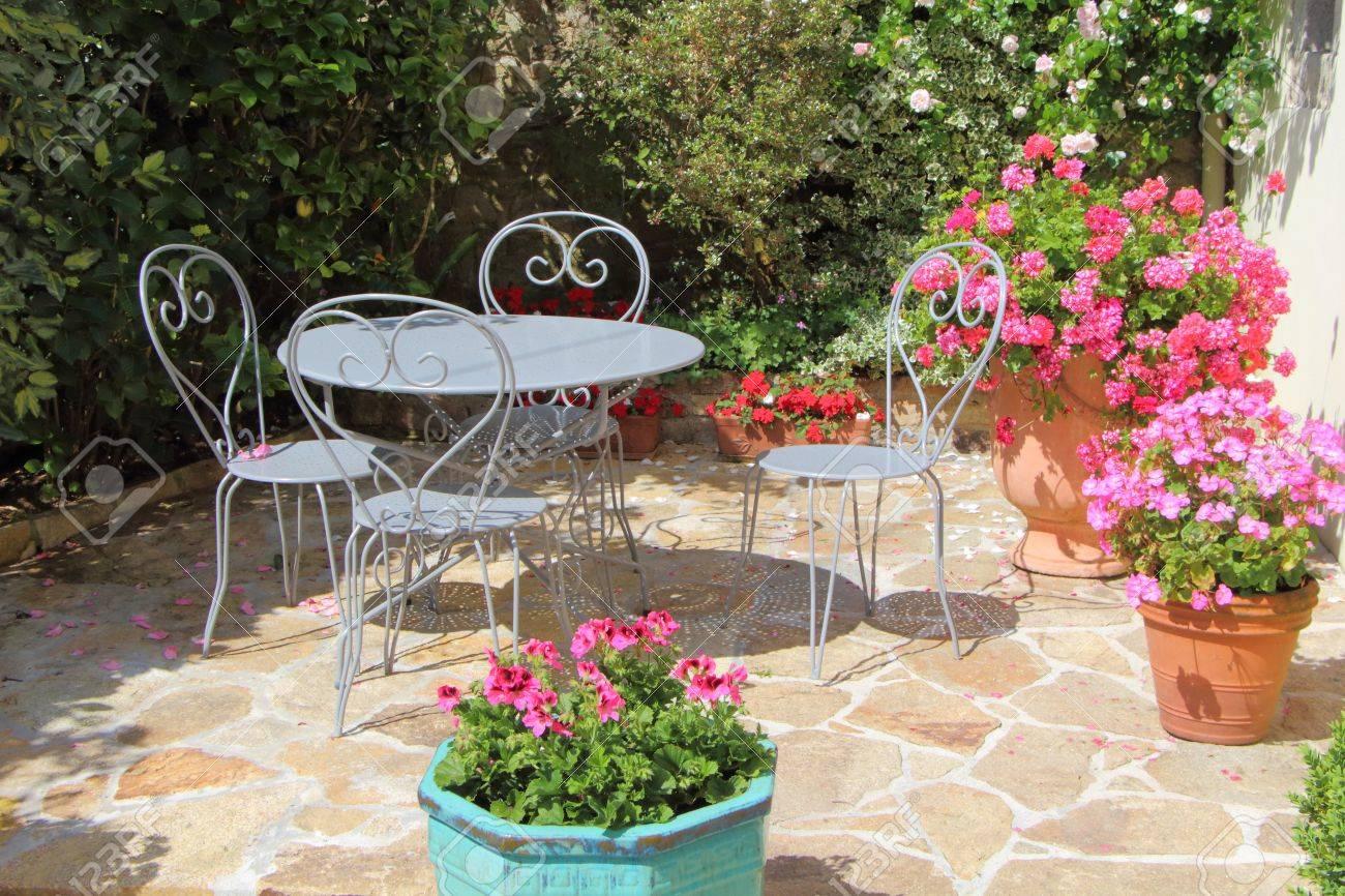 Terraza Florecida Con Geranio En Macetas Y Muebles De Jardín De ...