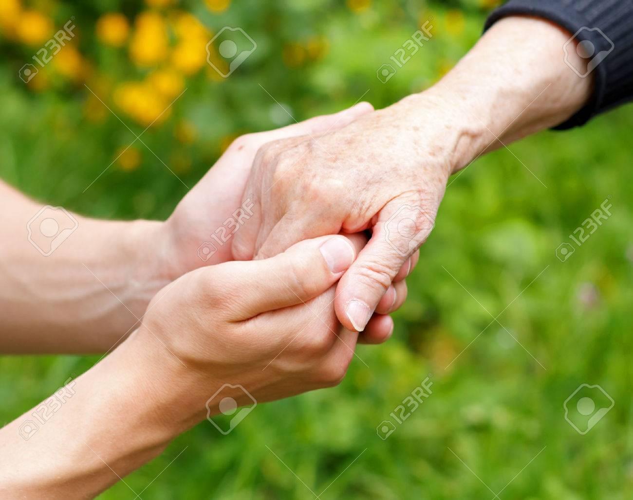 Doctor's hand holding a wrinkled elderly hand - 27901415