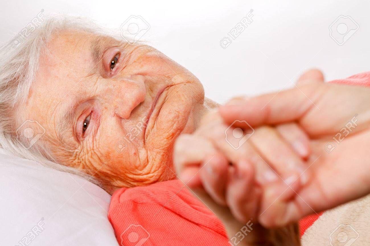 Caregiver holding elderly patients hand at home - 49825893