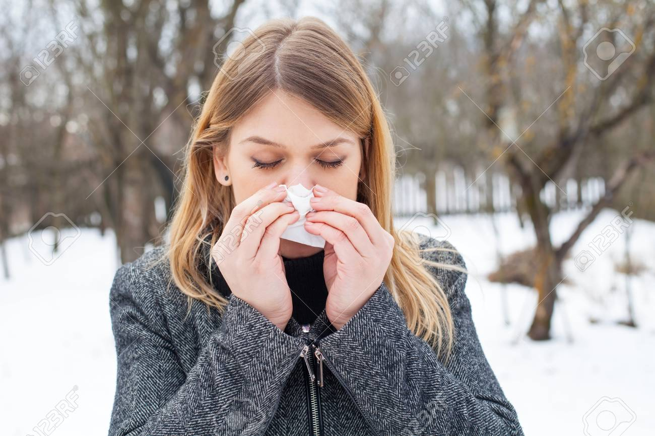 Picture of a sick young woman blowing her nose outdoor - 70759701