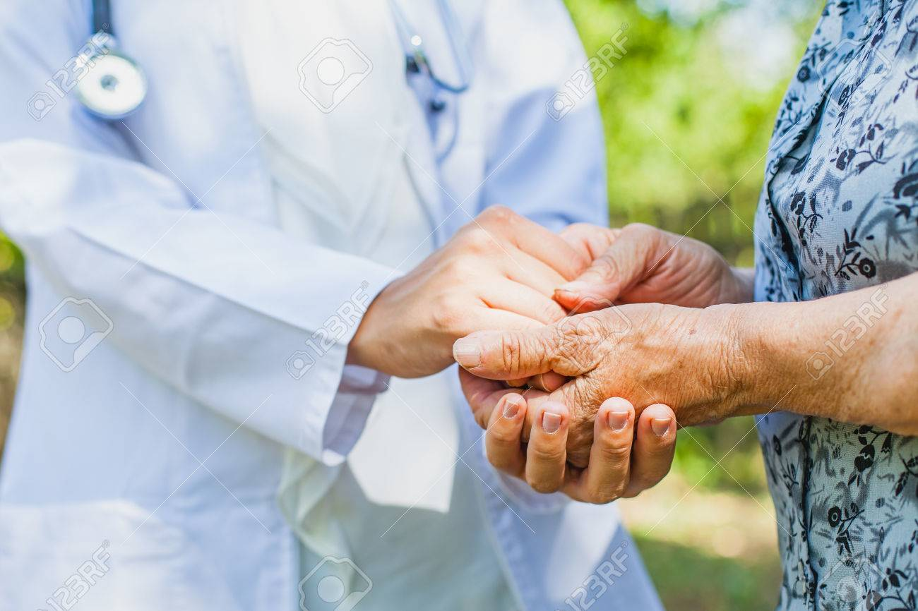 Close up medical doctor holding senior woman's shaking hands, Parkinson disease - 85247822