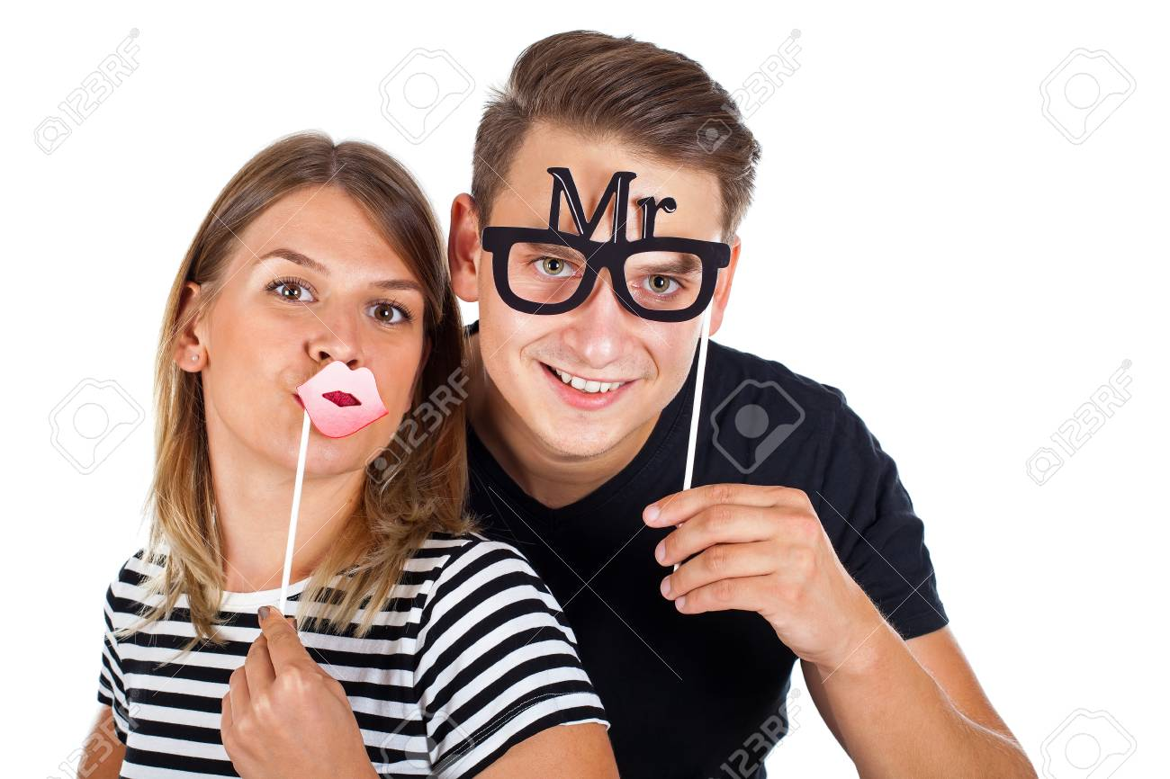 Picture of a happy couple posing with photobooth accesories on isolated background - 87159016