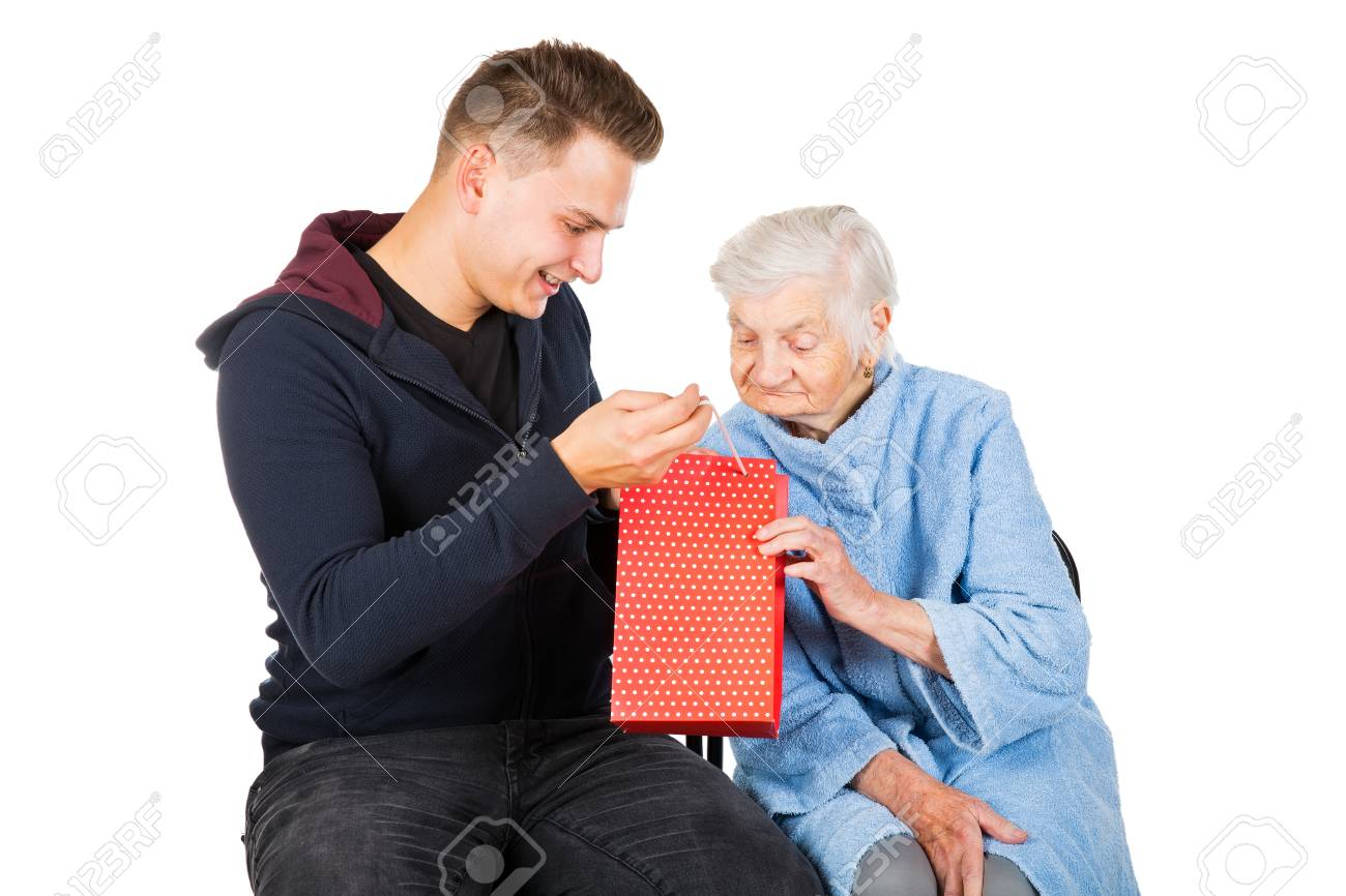 Picture Of An Old Lady Receiving Birthday Gifts From Her Grandson Stock Photo