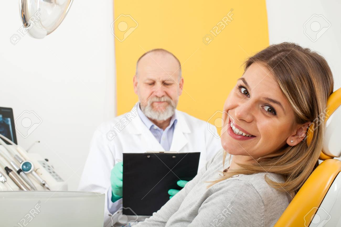 Smiling female patient sitting in the dentist chair while doctor