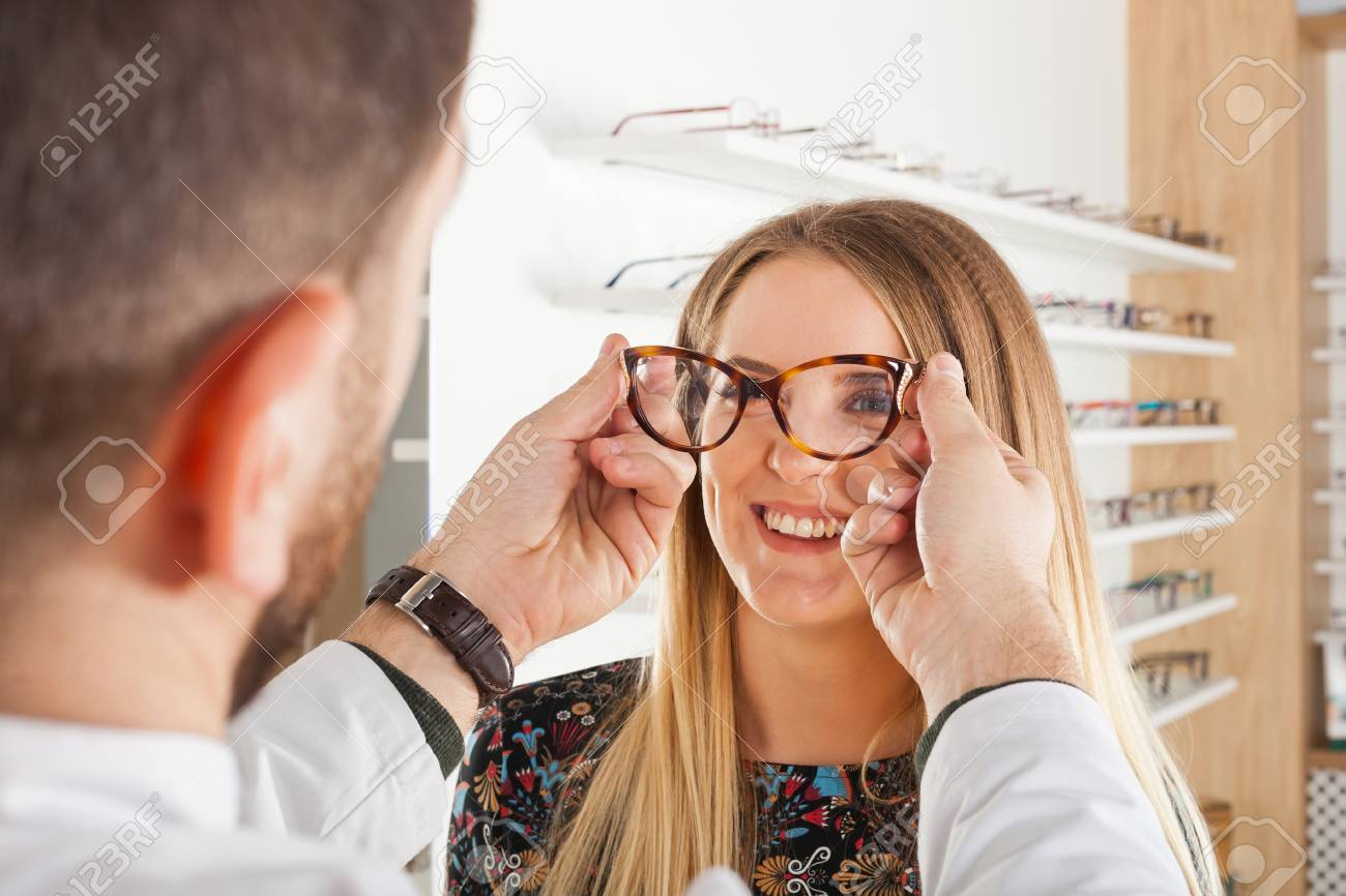Friendly male ophthalmologist choosing eyeglass frame for beautiful young woman in an optical store - 97877014