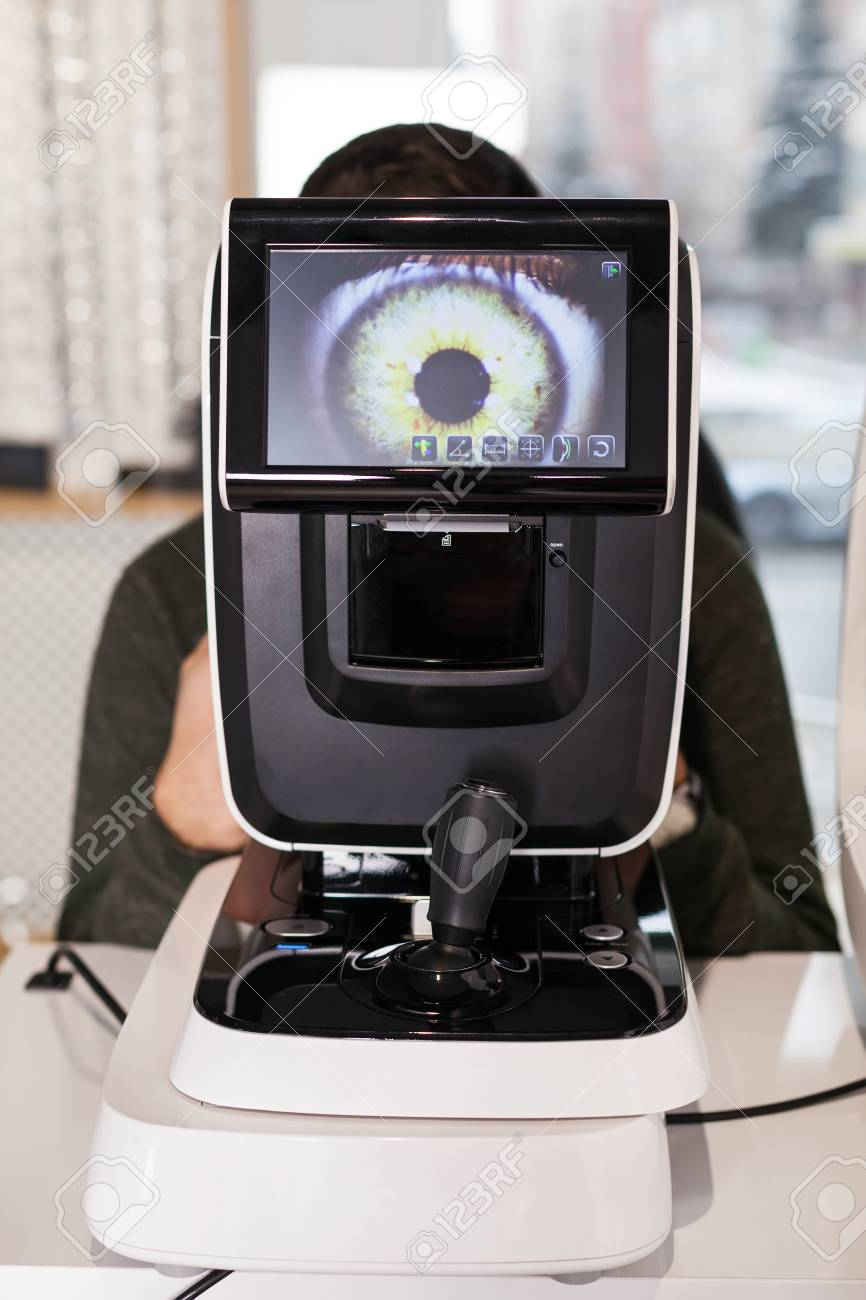 Ophthalmologist examining young man with optometric machine in optics store - 108692675