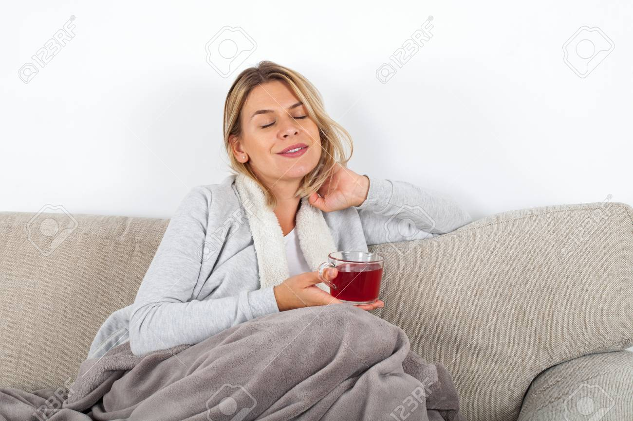 Beautiful woman relaxing on the sofa and drinking hot tea, wrapped in a grey blanket - 110839755