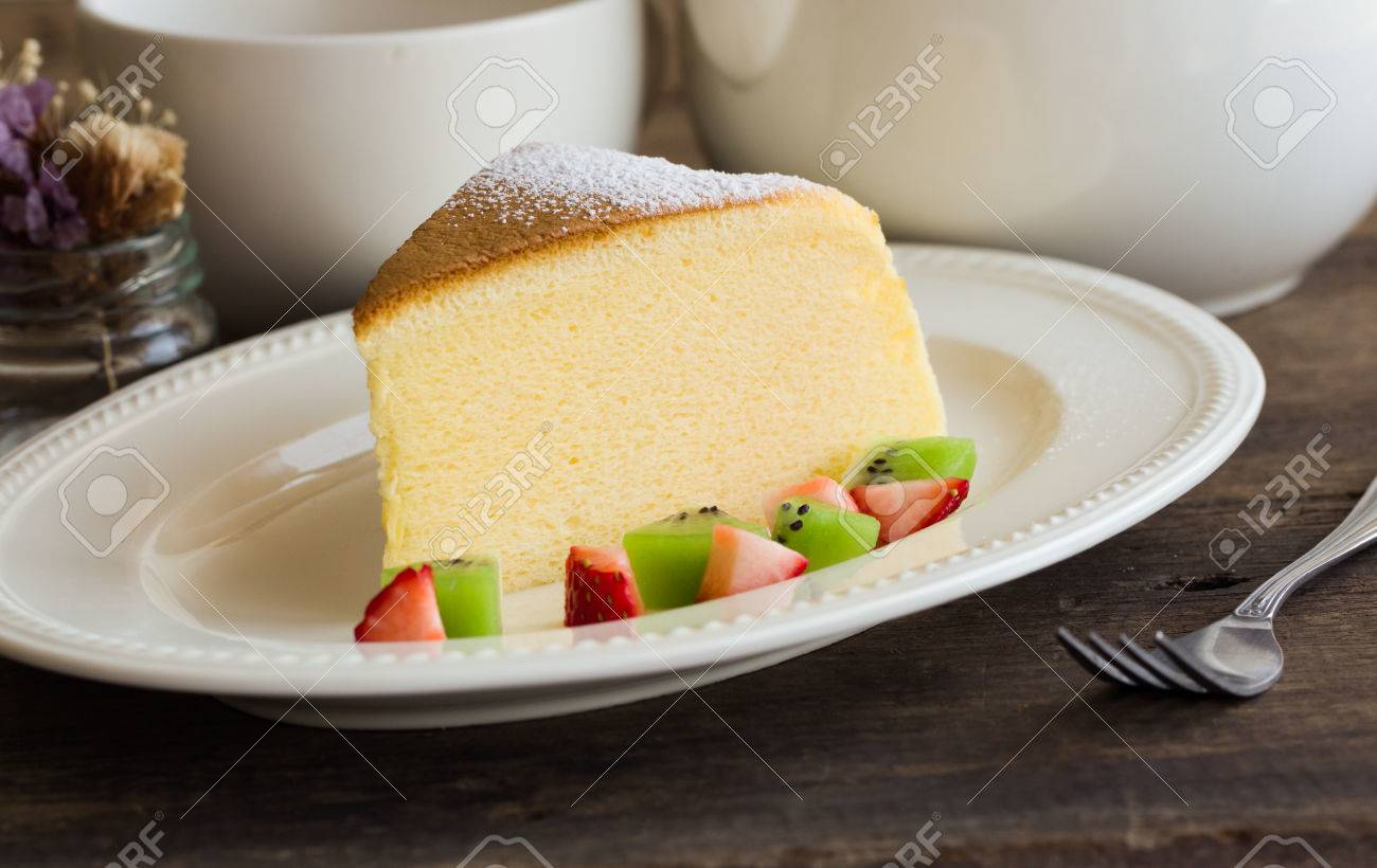 Homemade Japanese cheesecake. Absolutely delicious, fluffy,lite and soft. Serve with sparkling icing, fresh fruit such as kiwi and strawberry on white plate put on wood table for your relax time. Low fat bakery. - 78334704