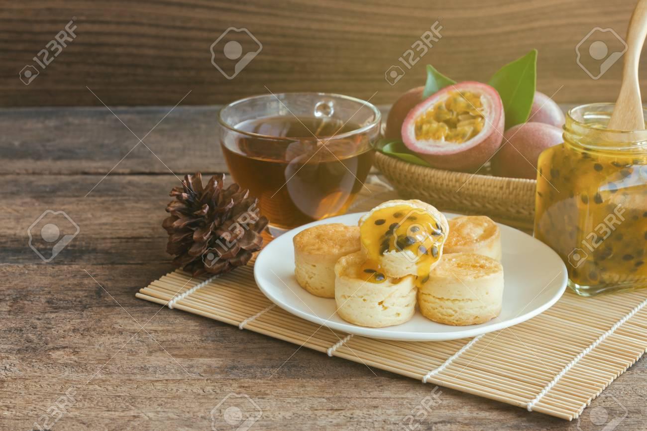 自家製の美味しいプレーンのスコーンは パッション フルーツ ジャムと背景や壁紙の木製テーブル コピー スペースでお茶を添えます スコーンはアフタヌーン ティーやコーヒー ブレークの伝統的な英語のペストリーです の写真素材 画像素材 Image