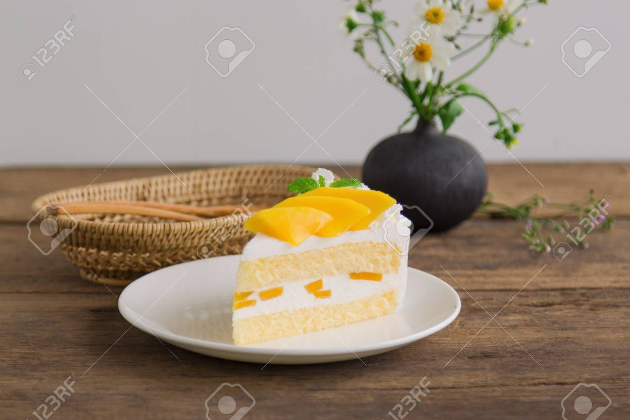 Homemade mango shortcake,sponge cake or soft cake on white plate decorate with ripe mango and mint on wood table. Mango is tropical fruits that make feel fresh on summer time. Sweet and sour dessert. - 89370339