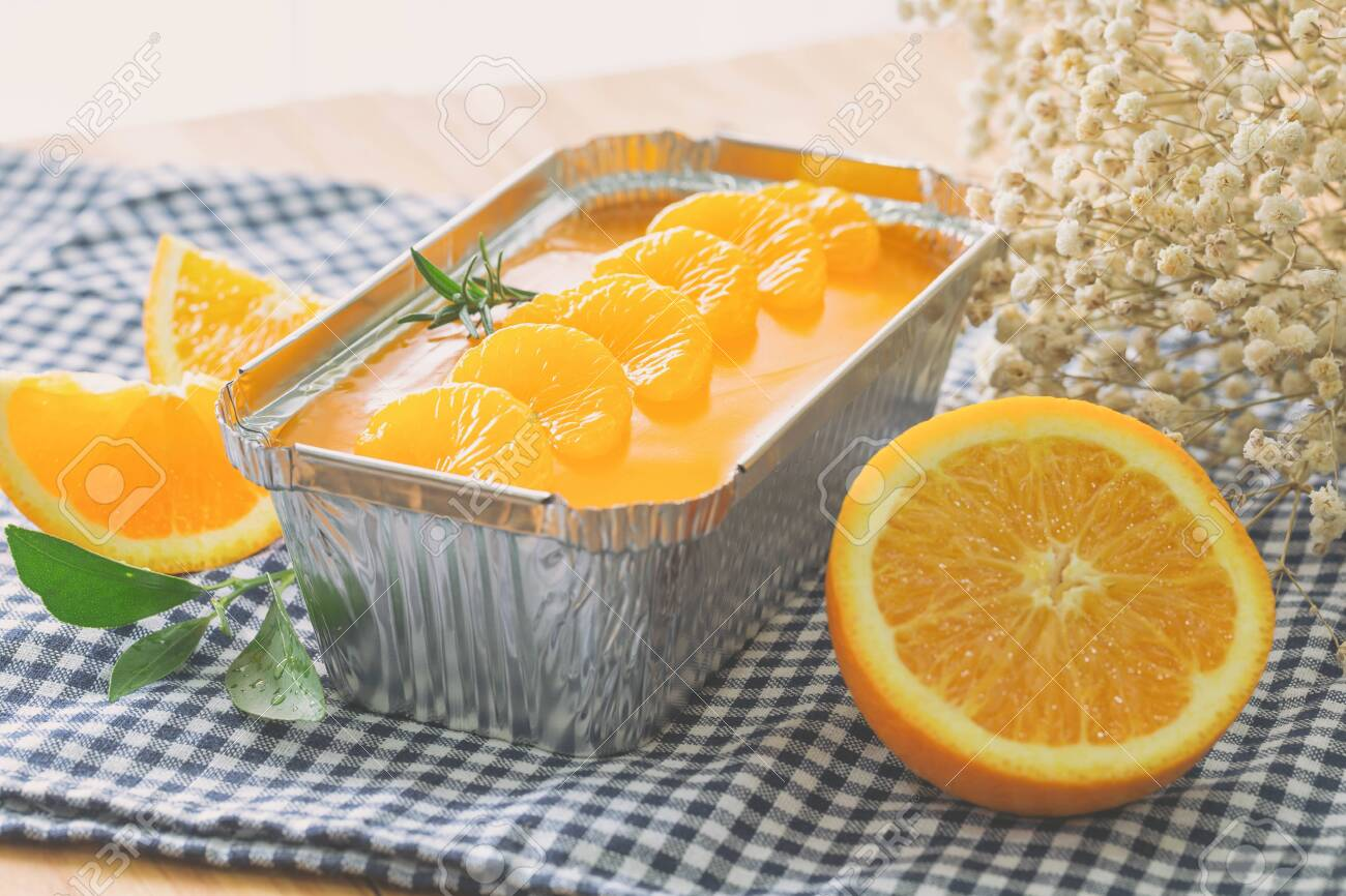 Fresh baked sweet and delicious mandarin orange sponge cake decoration with orange jelly sauce and orange pulp in aluminum foil loaf put on wood table in side view. Homemade bakery concept for cafe. - 153512509