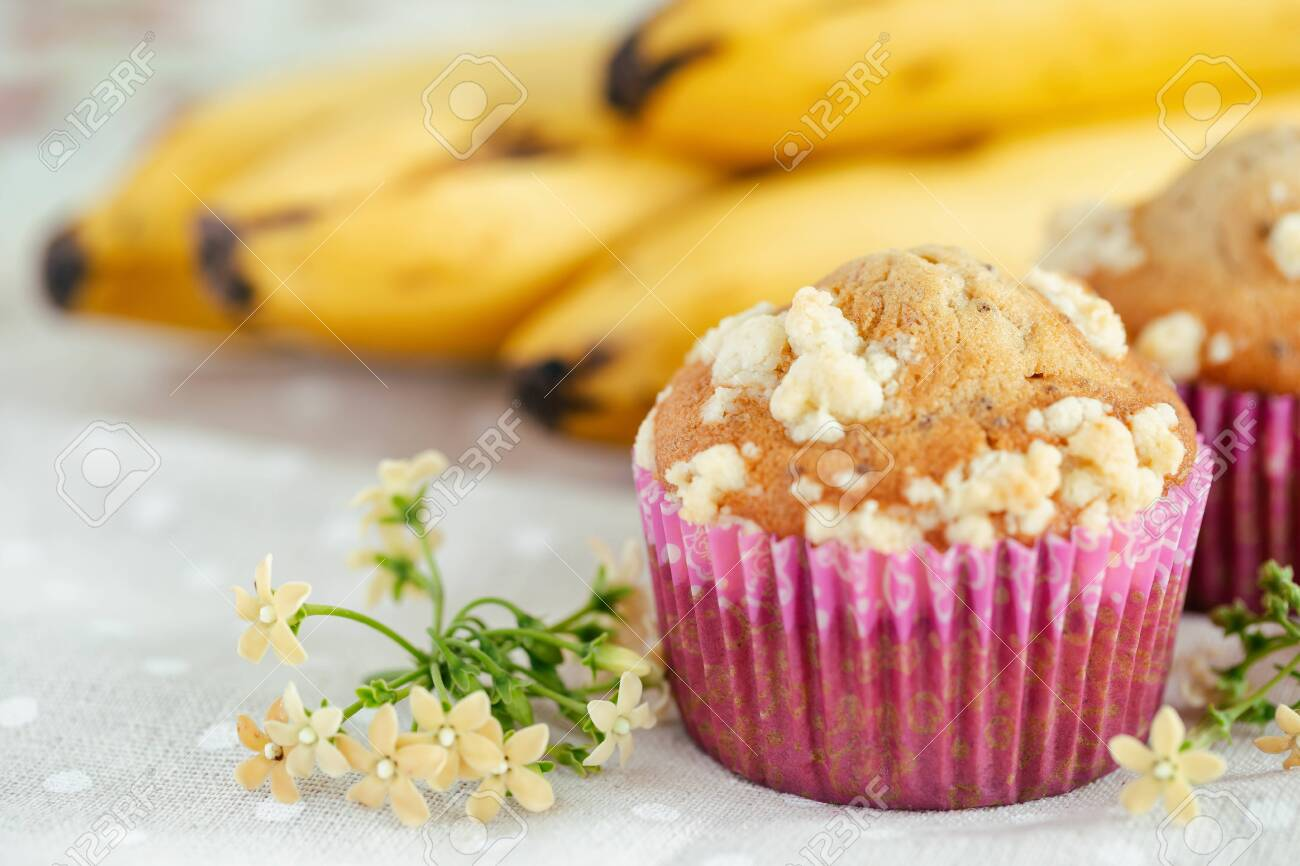 Piece of banana crumble and sesame cupcake or muffin in mini pink cup on table with copy space. Banana cupcake topping with crumbles so sweet and tasty. Homemade bakery with simply delicious concept. - 156398977