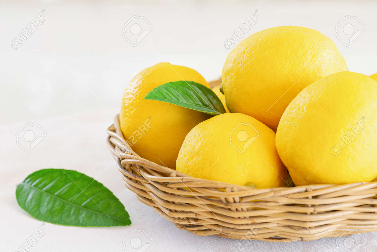 Group of whole organic lemon in wood basket on white background. Fresh lemon have high vitamin C and delicious sour taste for lemonade or cooking. Citrus or citron fruit concept. - 165419602