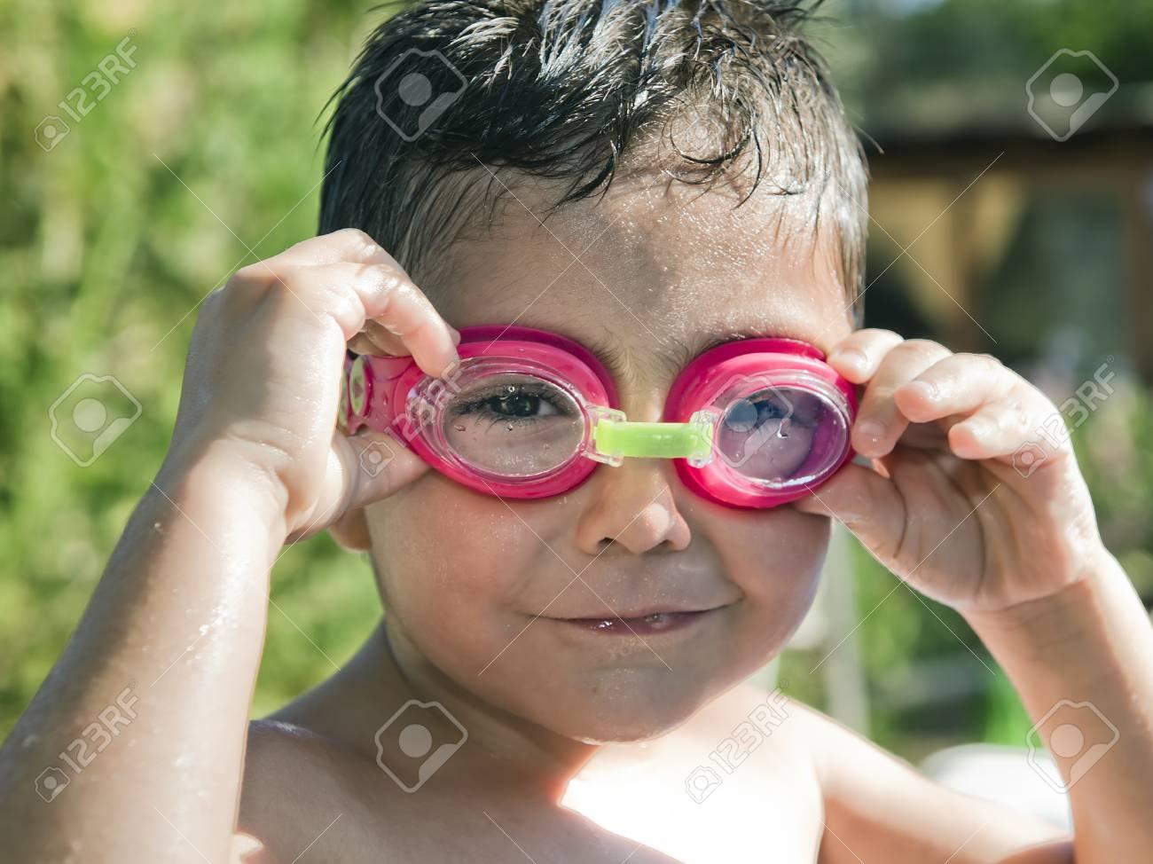 05ef571a1 Verano Retrato De Un Niño Lindo En Vacaciones En La Piscina Con Gafas De  Agua En. El Chico Está Mojado Después Del Baño Y Sonríe Con Complicidad  Mientras ...