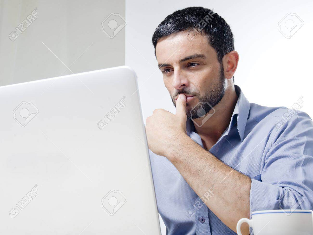 Young Man with Beard Working on Laptop isolated on a White Background Stock Photo - 21648331
