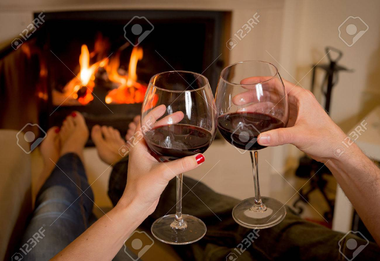 close up of young couple drinking wine in front of an open wood fire Stock Photo - 24921808