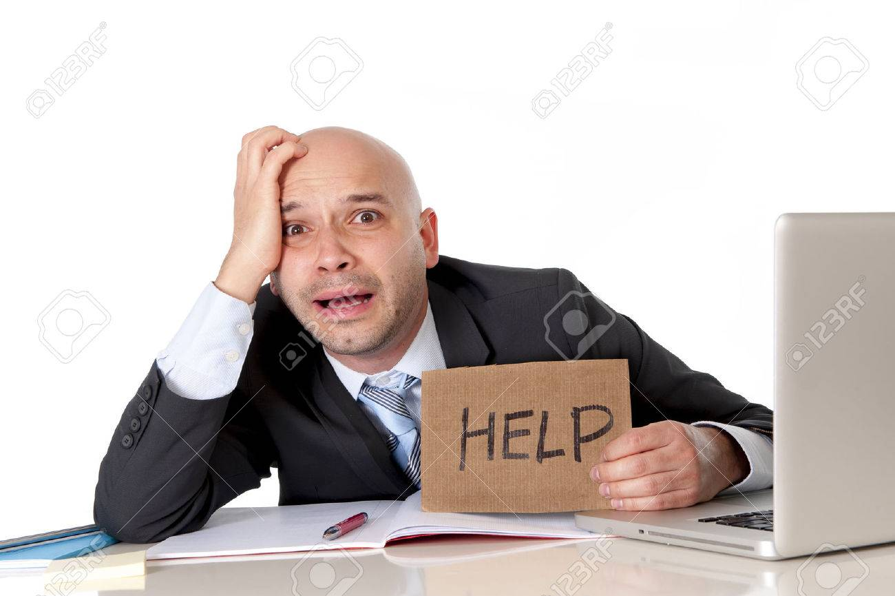 overworked unhappy bald business man in stress wearing suit stock photo overworked unhappy bald business man in stress wearing suit holding help sign working on computer