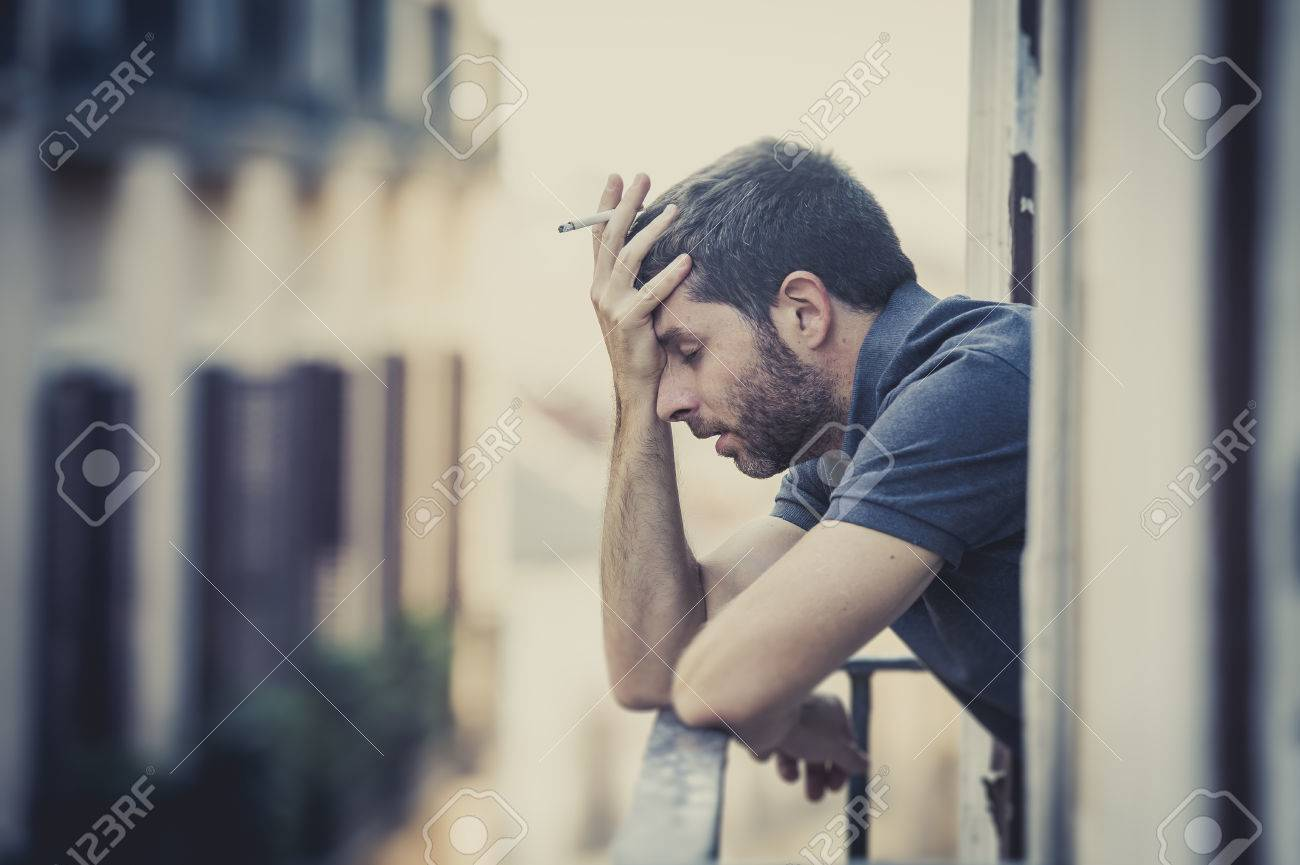 Stock photo young man alone outside at house balcony terrace smoking depressed destroyed wasted and sad suffering emotional crisis and depression