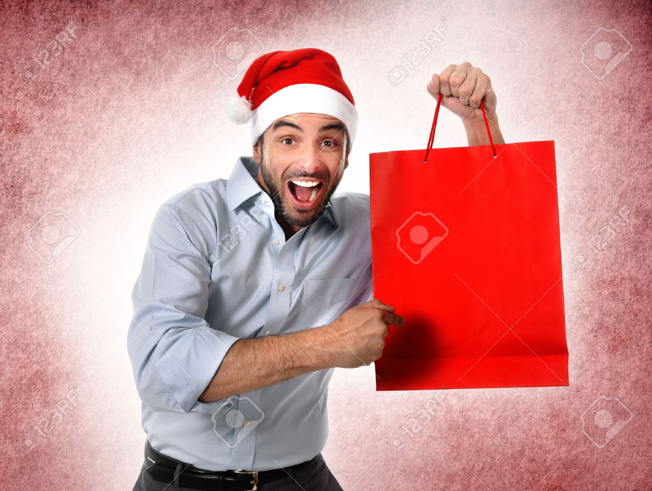Happy Man In Santa Hat Holding And Pointing Red Shopping Bag ...