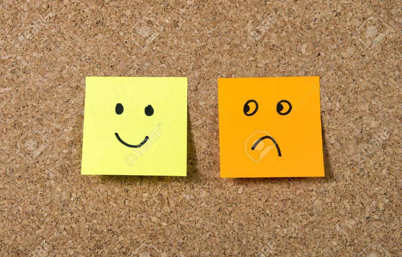 Two notes stuck on corkboard or message board with smiley and two notes stuck on corkboard or message board with smiley and sad cartoon face expression in biocorpaavc