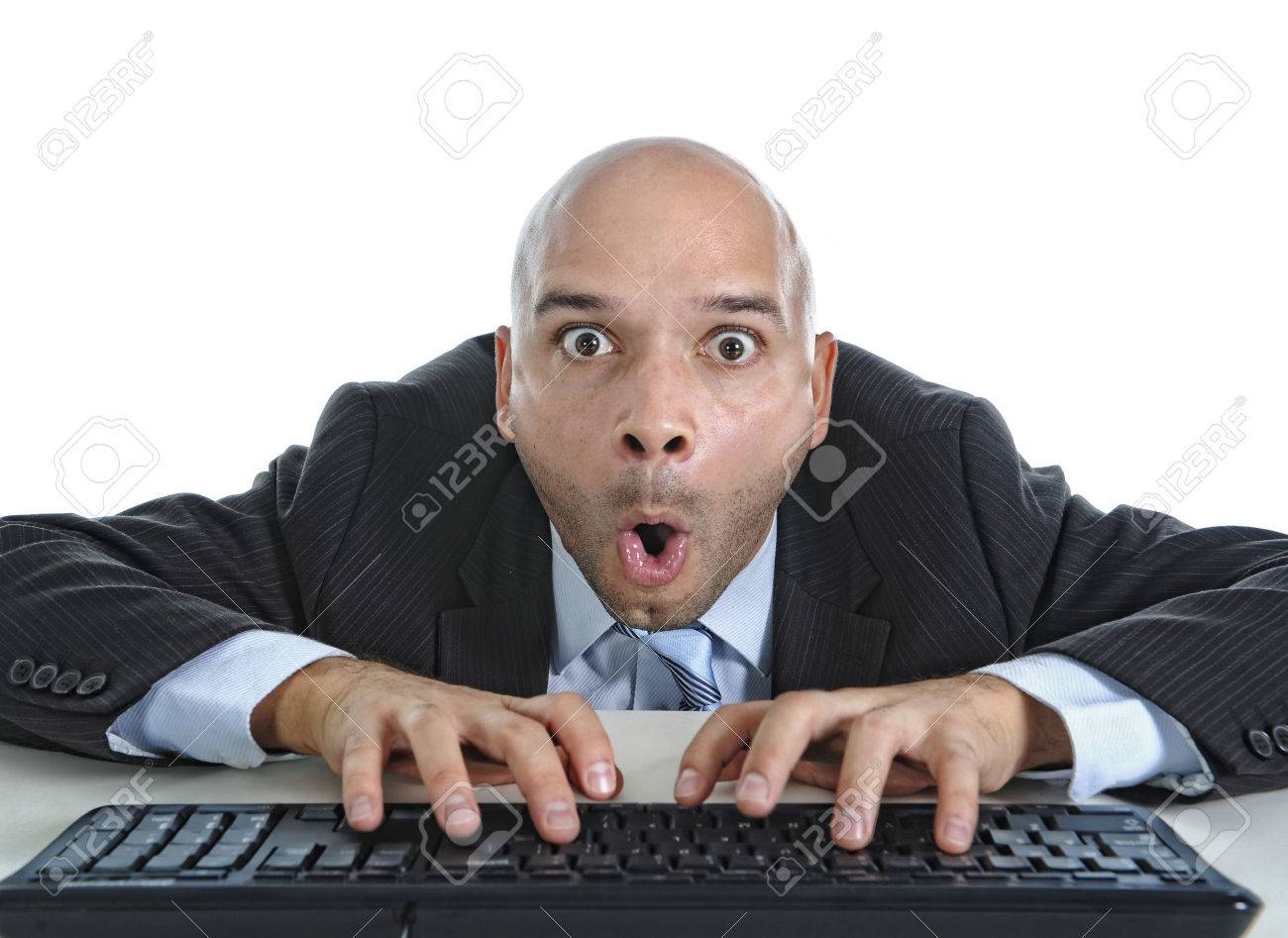 Stock Photo - young businessman typing on computer keyboard with funny face  expression on watching porn online and internet chat