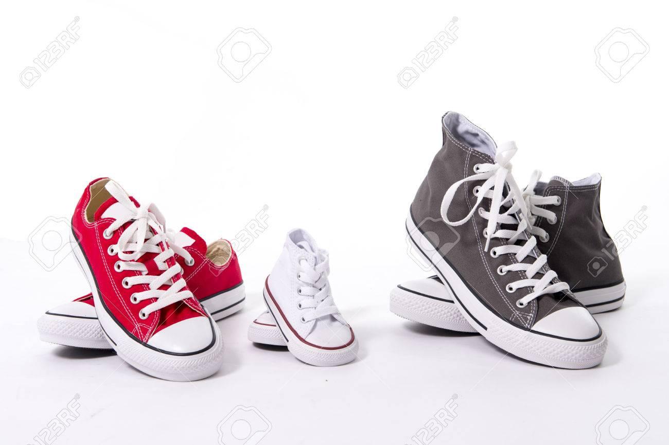 Tres pares de zapatos en el padre grande, mediano madre y el hijo o la hija pequeña de tamaño chico que representan la familia, el crecimiento, la