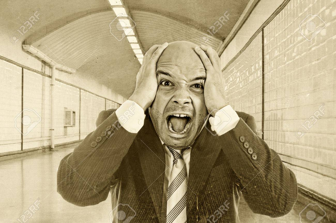 young desperate businessman fired from job screaming in stress stock photo young desperate businessman fired from job screaming in stress wearing suit and tie on street subway tunnel suffering and looking destroyed