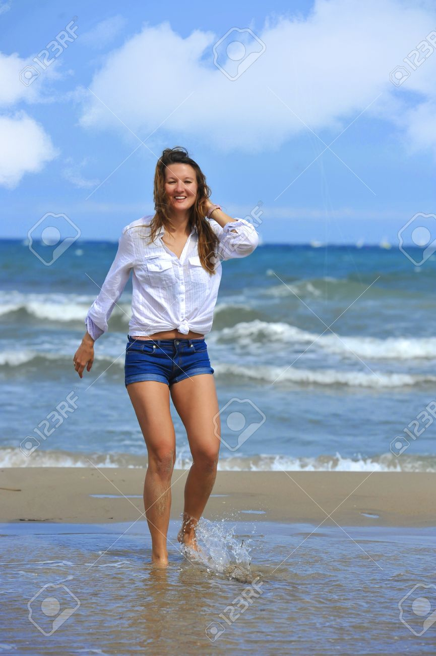 Young Beautiful Girl Walking On Water At Sea Shore Wearing Shorts ...
