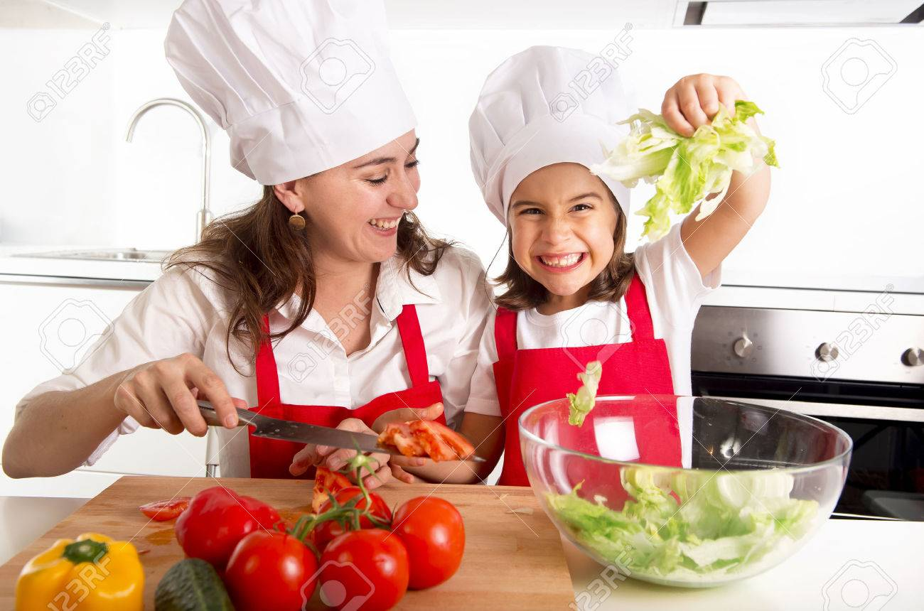 young mother preparing salad for lunch wearing apron and cook hat at home kitchen with little daughter playing with lettuce and having fun together in healthy nutrition education concept - 45948163