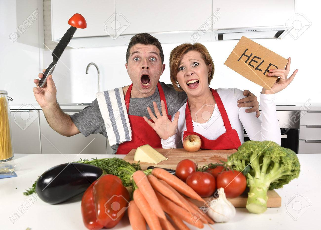 amateur young couple young attractive American couple in stress at home kitchen looking lost and  frustrated wearing apron asking