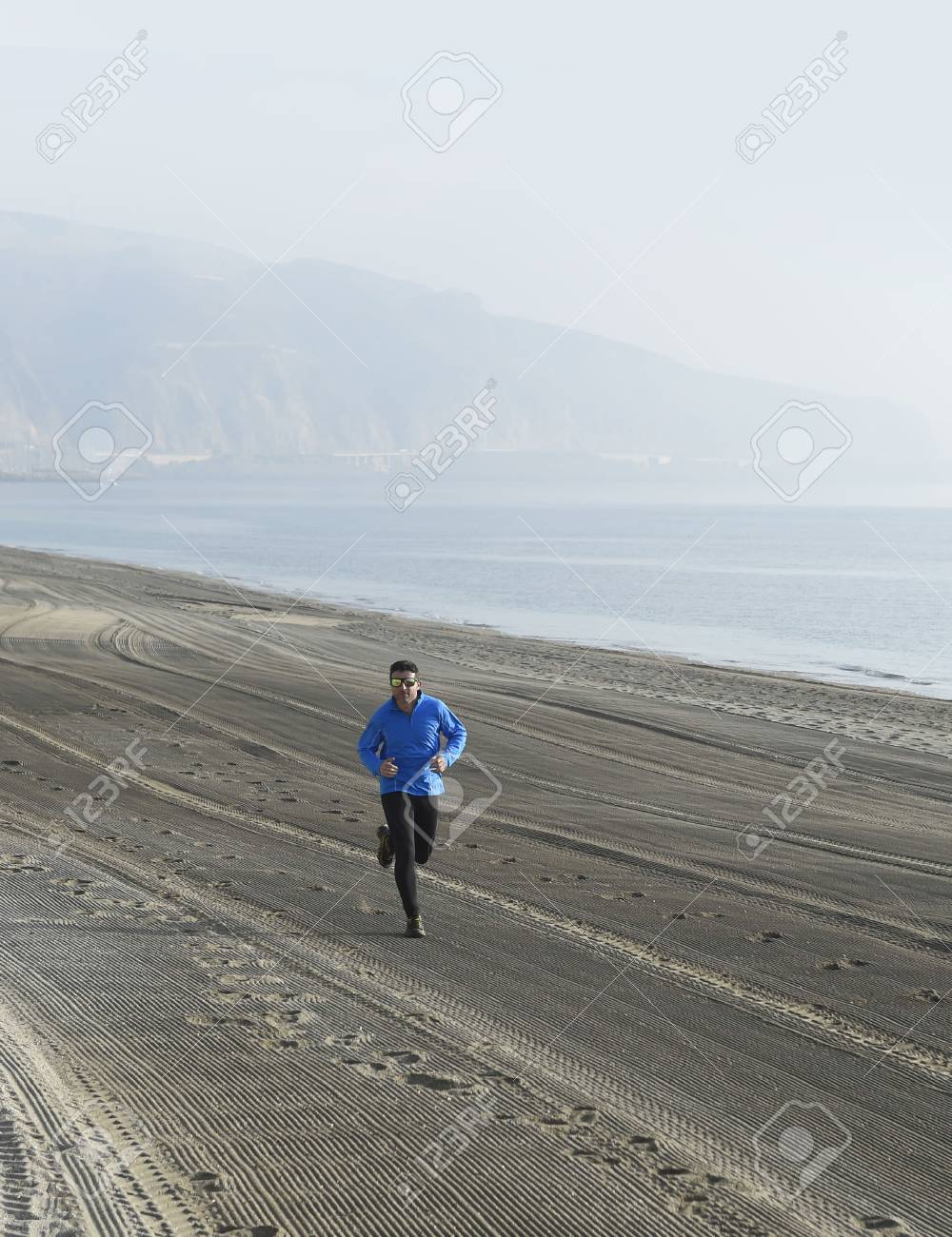 Stock Photo Young Sport Man Running Alone On Desert Beach Along The Sea Shore Training Workout On A Foggy And Overcast Winter Early Morning In Fitness And
