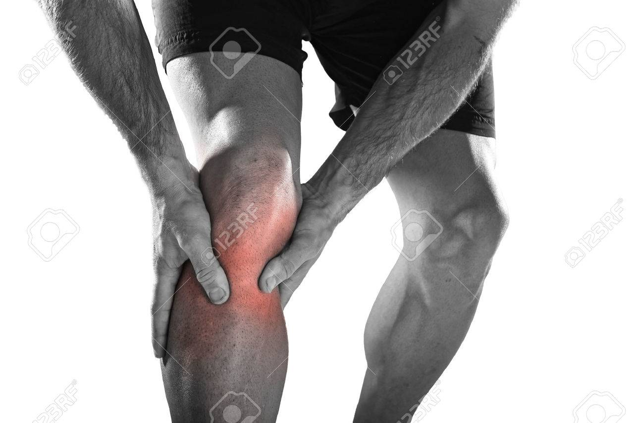 young sport man with strong athletic legs holding knee with his hands in pain after suffering ligament injury during a running workout training isolated on white background in black and white - 52285043