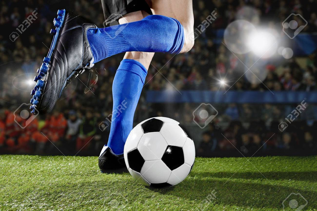 close up legs and feet of football player in action wearing blue socks and black shoes running and dribbling with the ball playing match on green grass pitch at soccer stadium with flashes and flares - 57688833