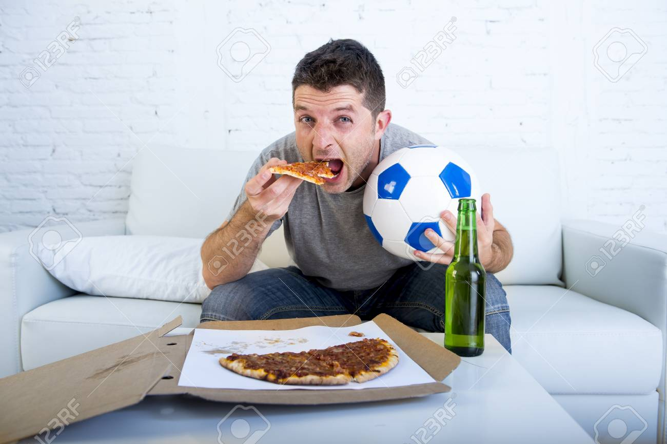 Stock Photo   Young Man Watching Football Game On Television Sitting On Sofa  Couch At Home Holding Soccer Ball Eating Pizza With Beer Bottle On The Table  ...