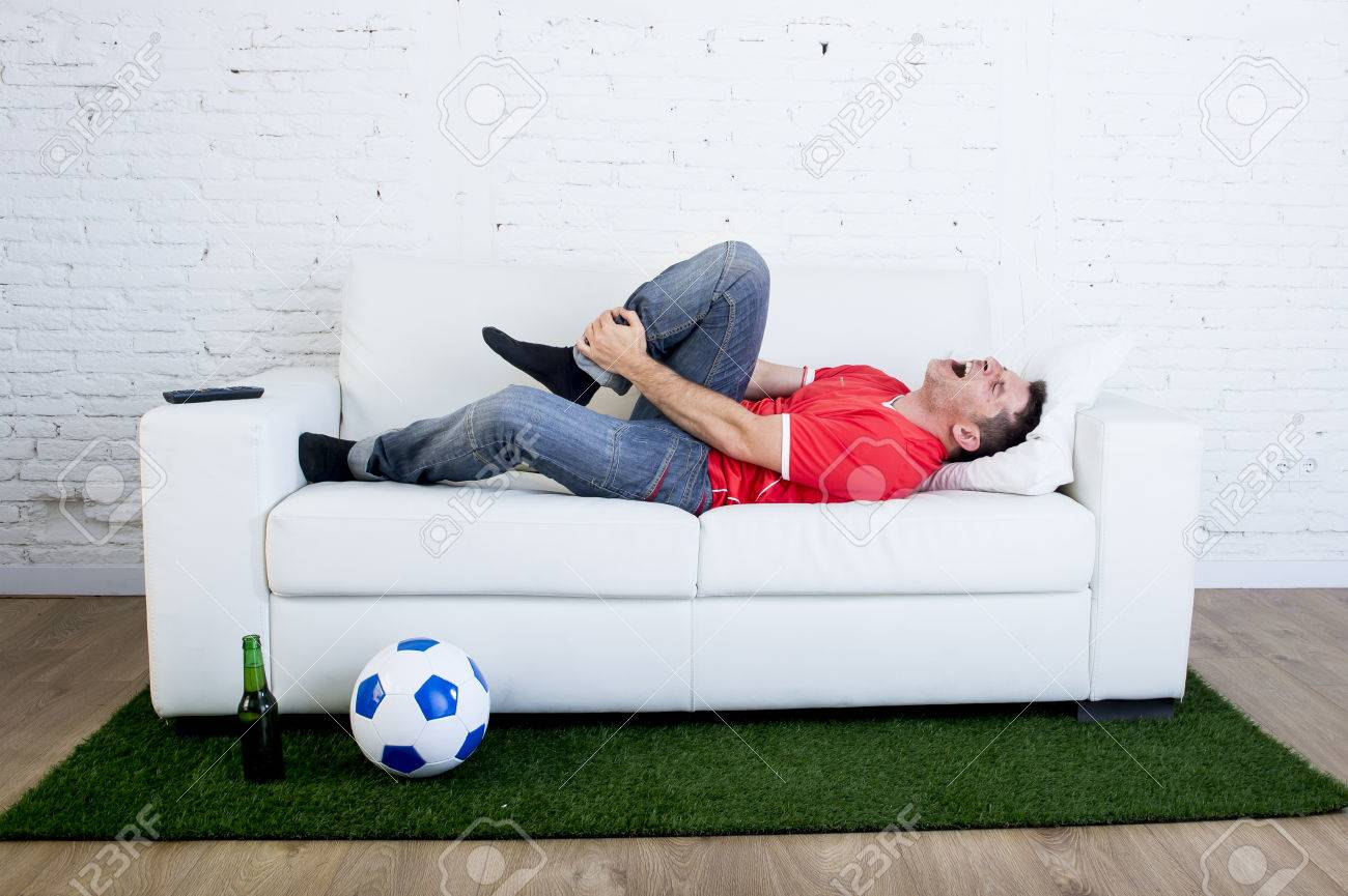 fanatic football fan lying on couch sofa with ball on green grass carpet  emulating soccer stadium