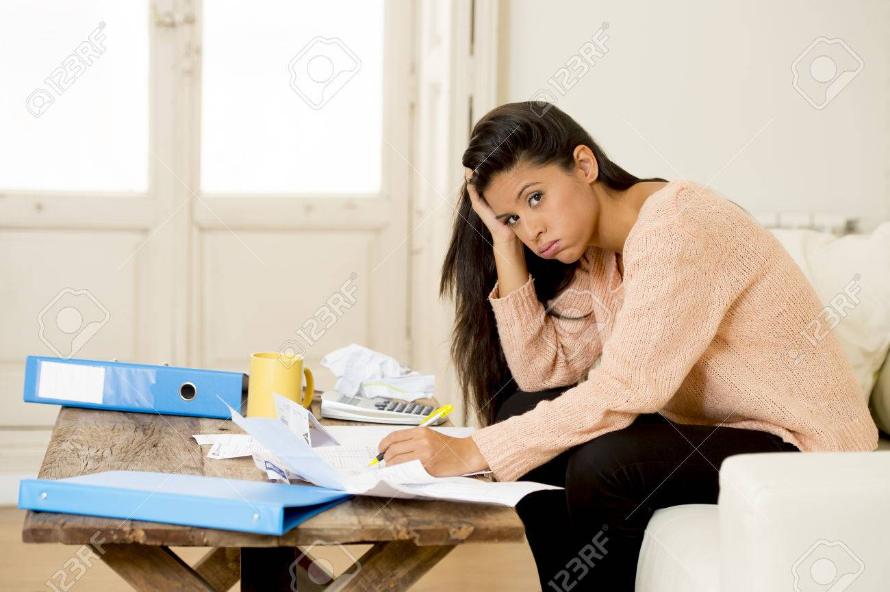Stock Photo   Young Sad Latin Woman At Home Living Room Couch Calculating  Monthly Expenses Worried In Stress With Bank Papers And Documents In Paying  Taxes ...