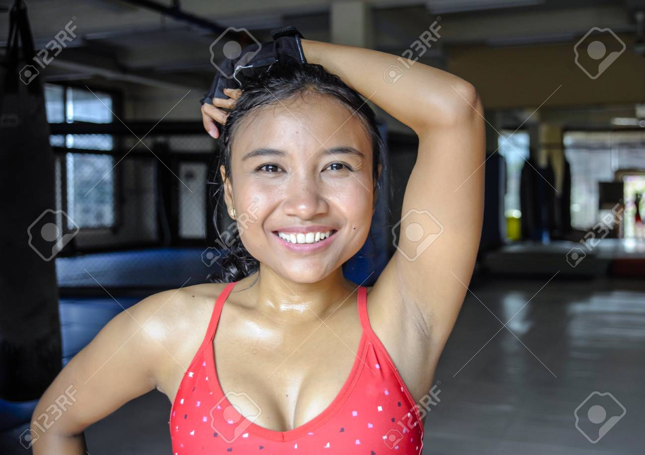 df2403e57f3 corporate portrait of happy beautiful and sweaty young Asian woman in sport  training cloths smiling relaxed
