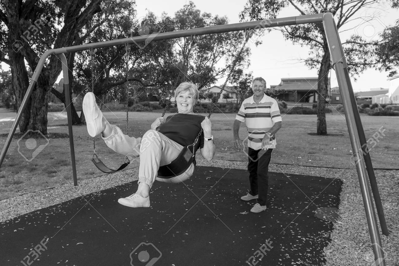 Black and white portrait of playful and happy senior american couple around 70 years old enjoying