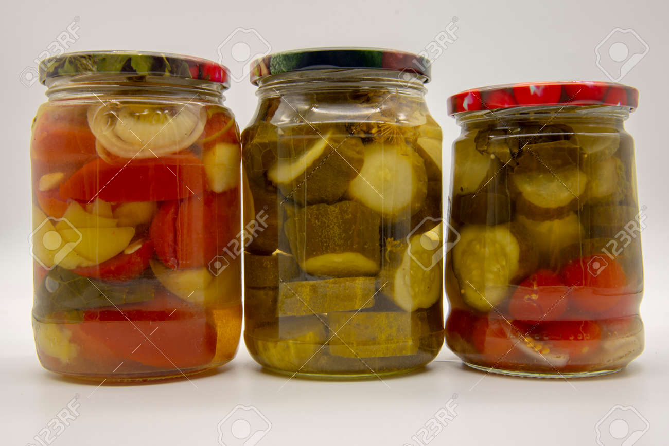 Three transparent jars with pickled vegetables, cucumbers, tomatoes and peppers, on a white background. - 158671540