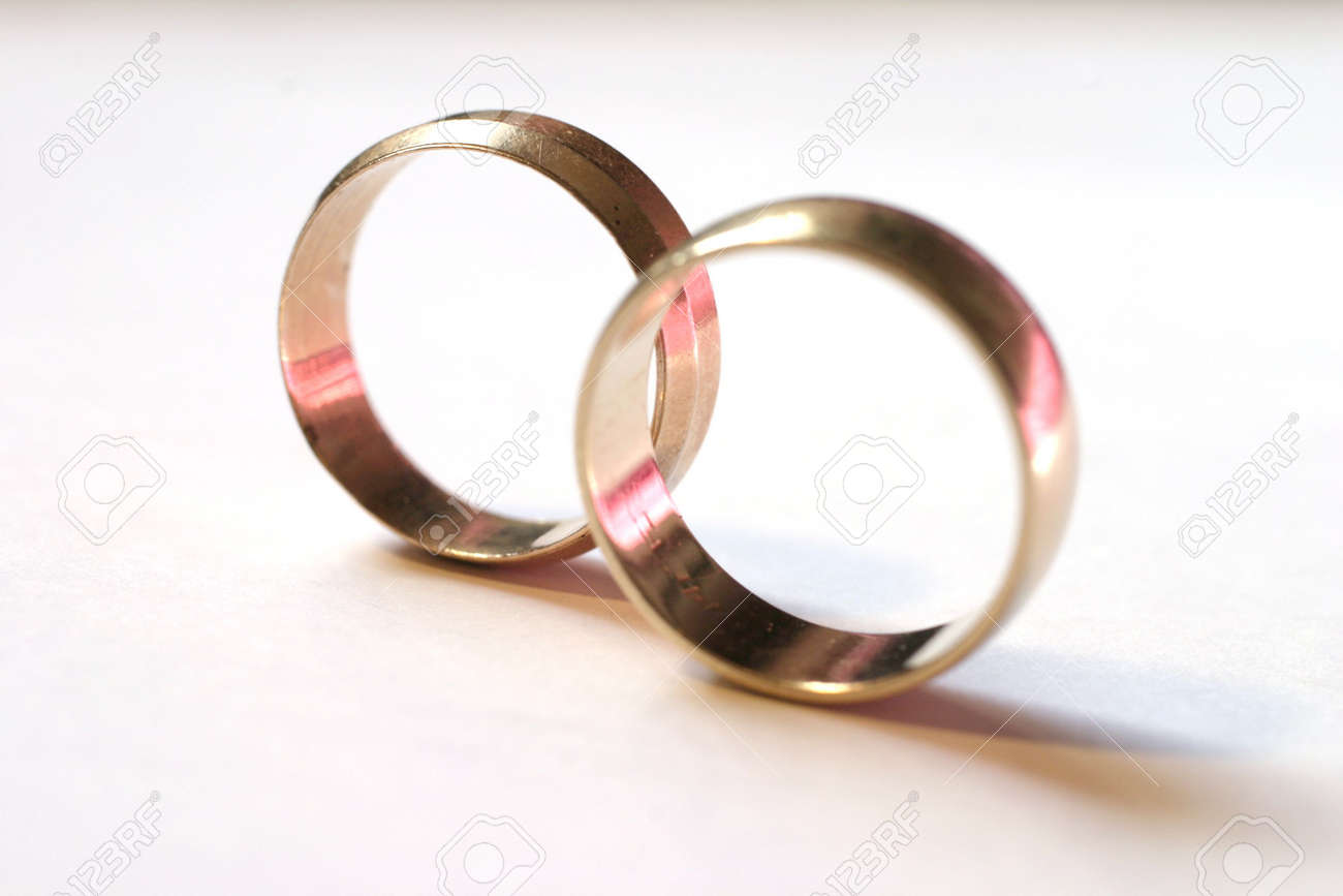 two gold wedding rings, pink reflections