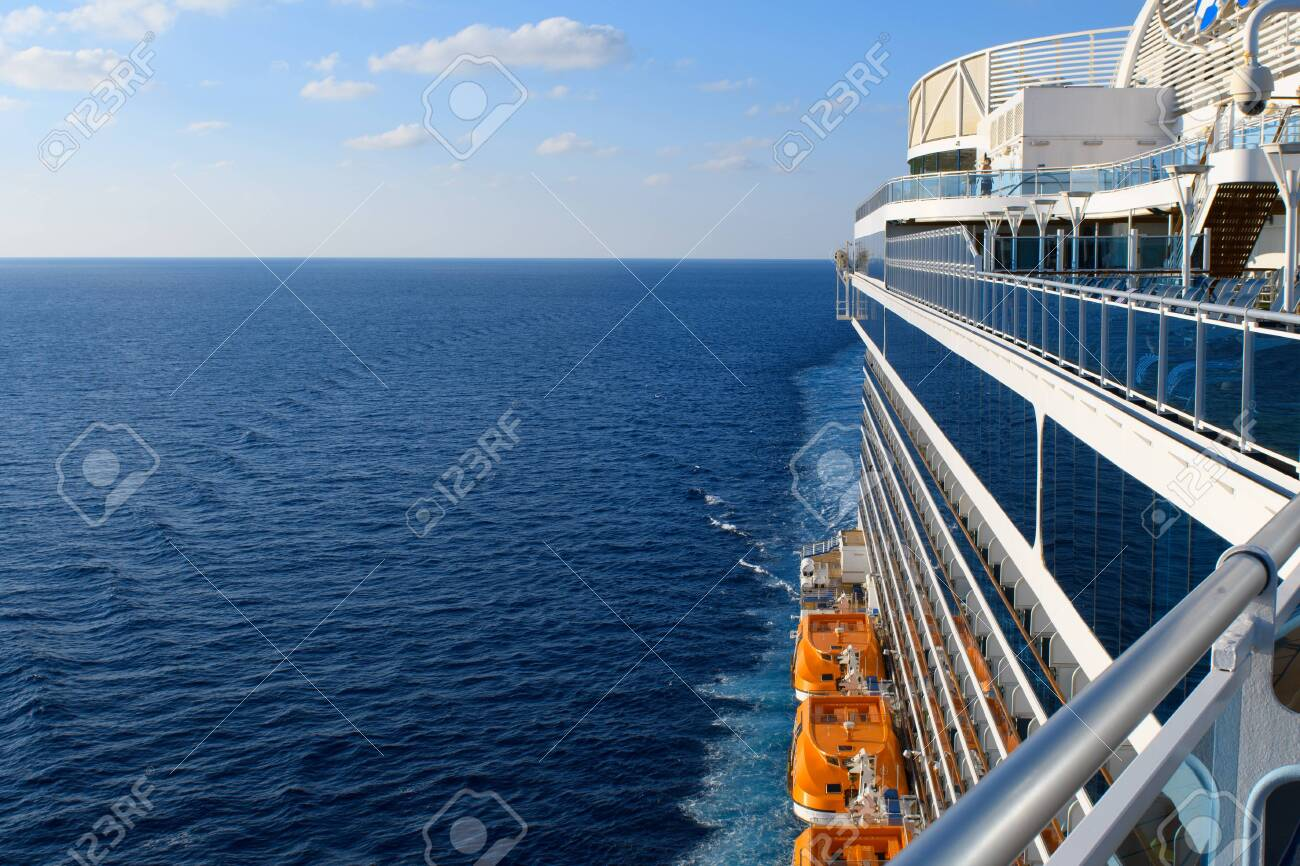Blue Atlantic ocean and white clouds above the horizon in blue sky with cruise ship perspective and orange lifeboats. - 131980905