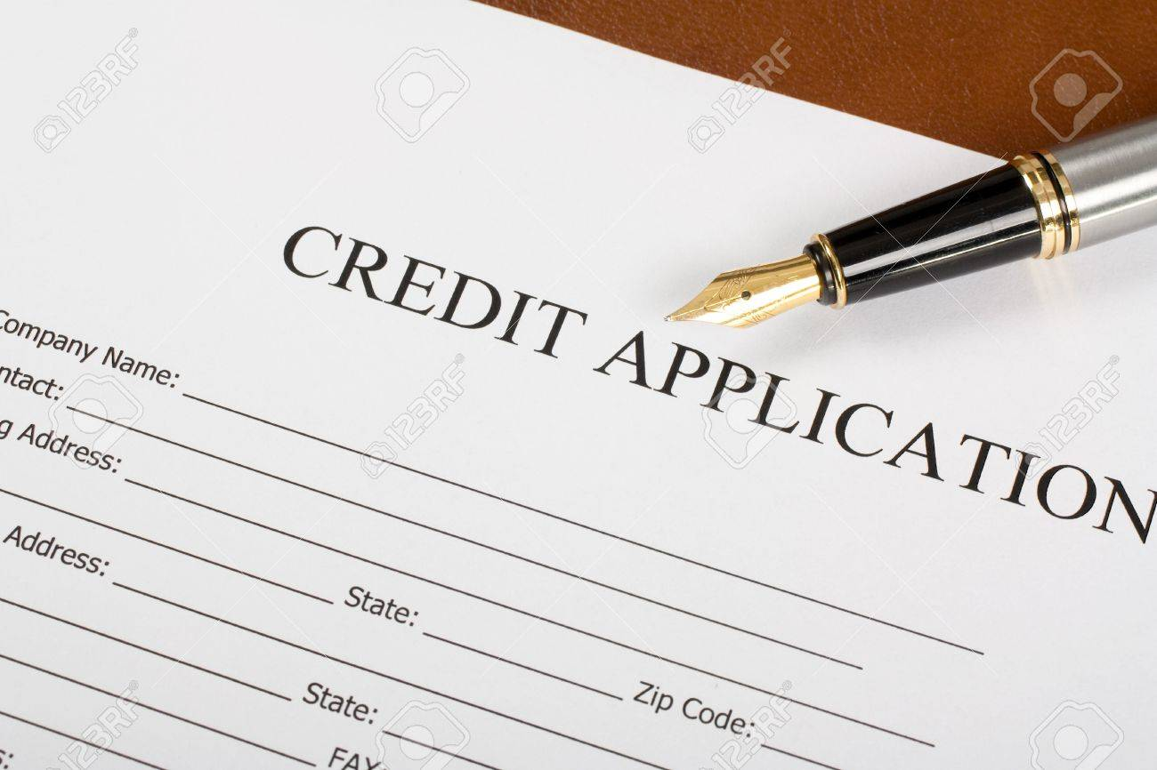 blank credit application form and pen on desktop stock photo