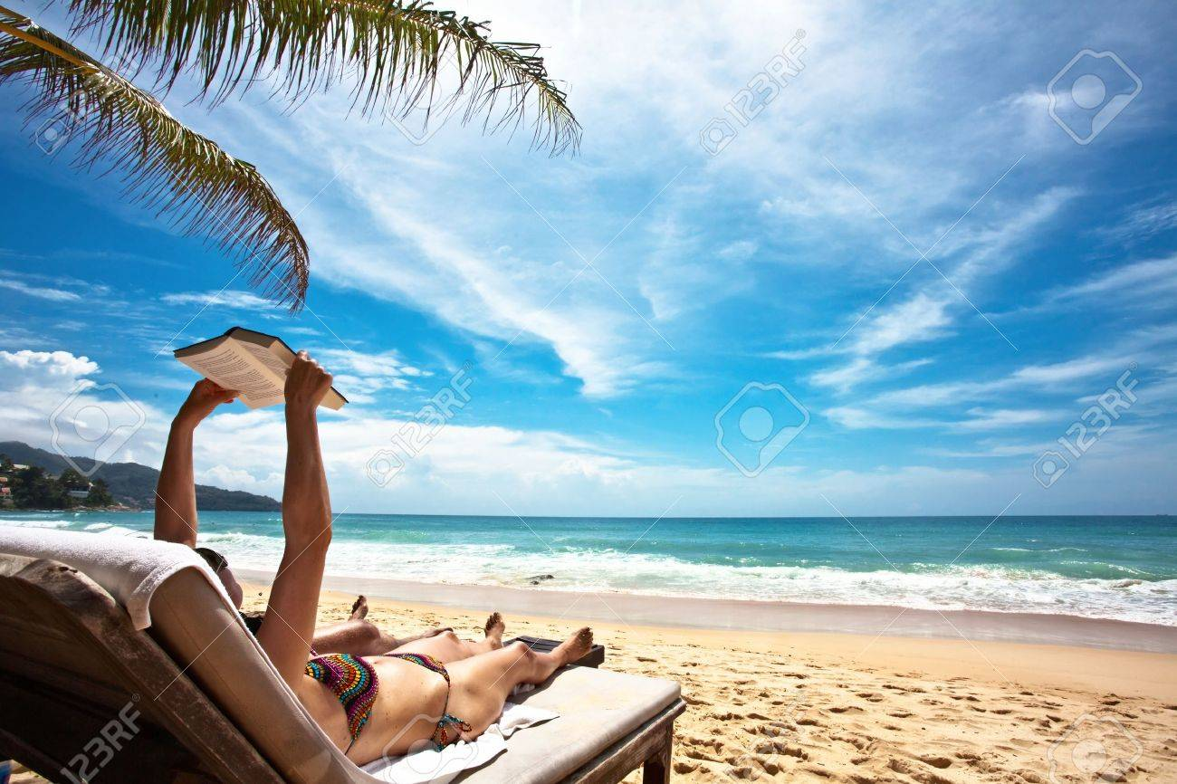 Relaxing and reading on the beach - 9237454