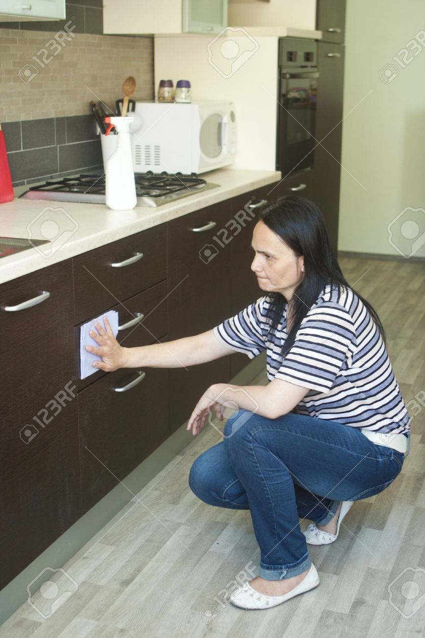 Adult Woman Kneeling To Clean The Lower Furniture Stock Photo  # Muebles Rodilla
