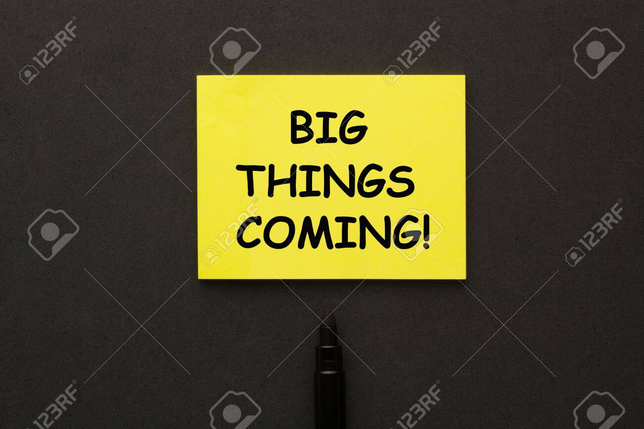 Big Things Coming written on yellow note with marker aside on black background. - 144260582