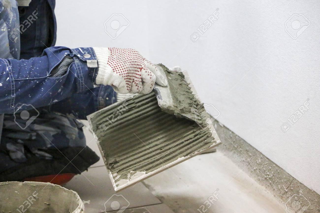 Repairs Laying Of Floor Ceramic Tiles Mens Hands In Gloves