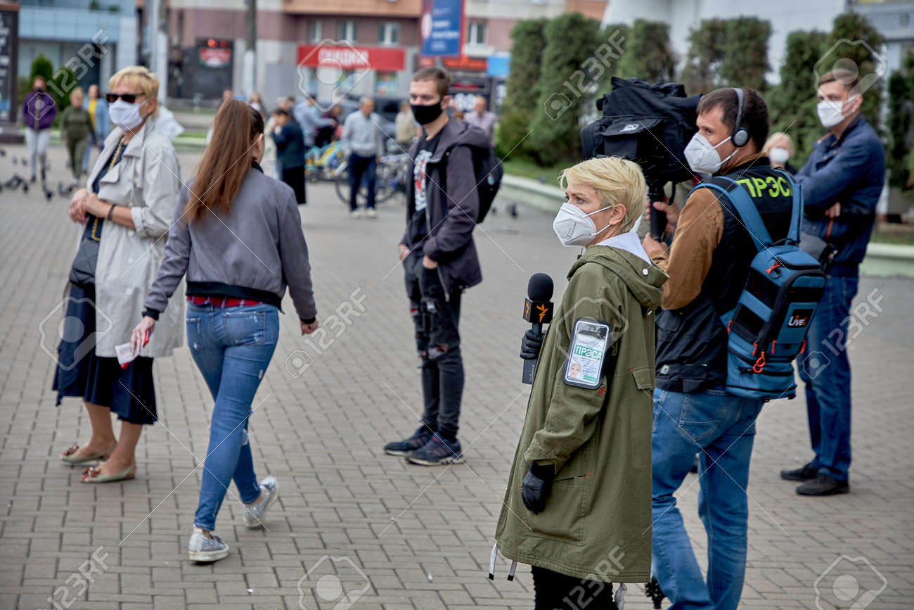 June 14 2020 Minsk Belarus Two reporters in masks walking on the street among the procession of people in masks - 151159311