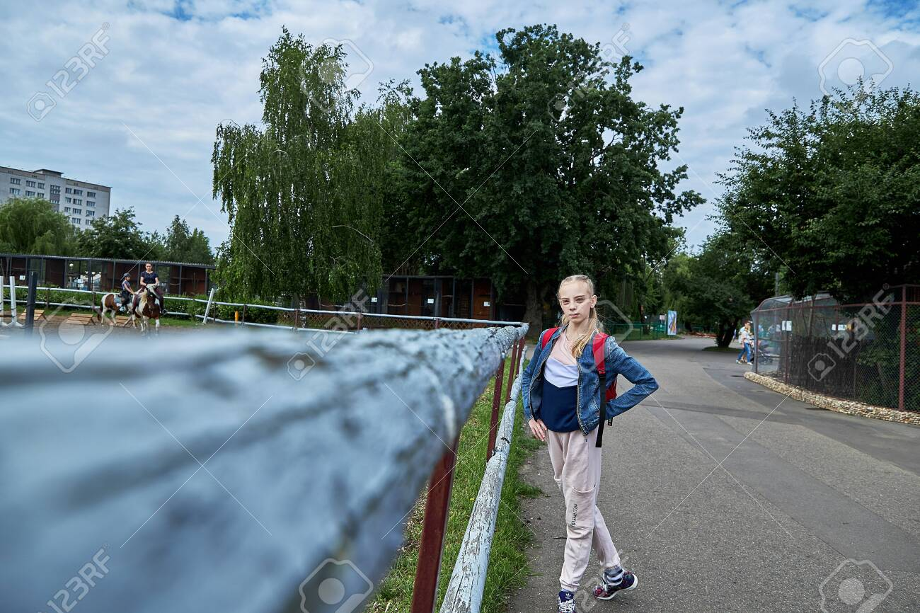 June 21 2020 Minsk Belarus A beautiful teenage girl stands next to an aviary where girls are engaged in equestrian sports on horses - 151228462