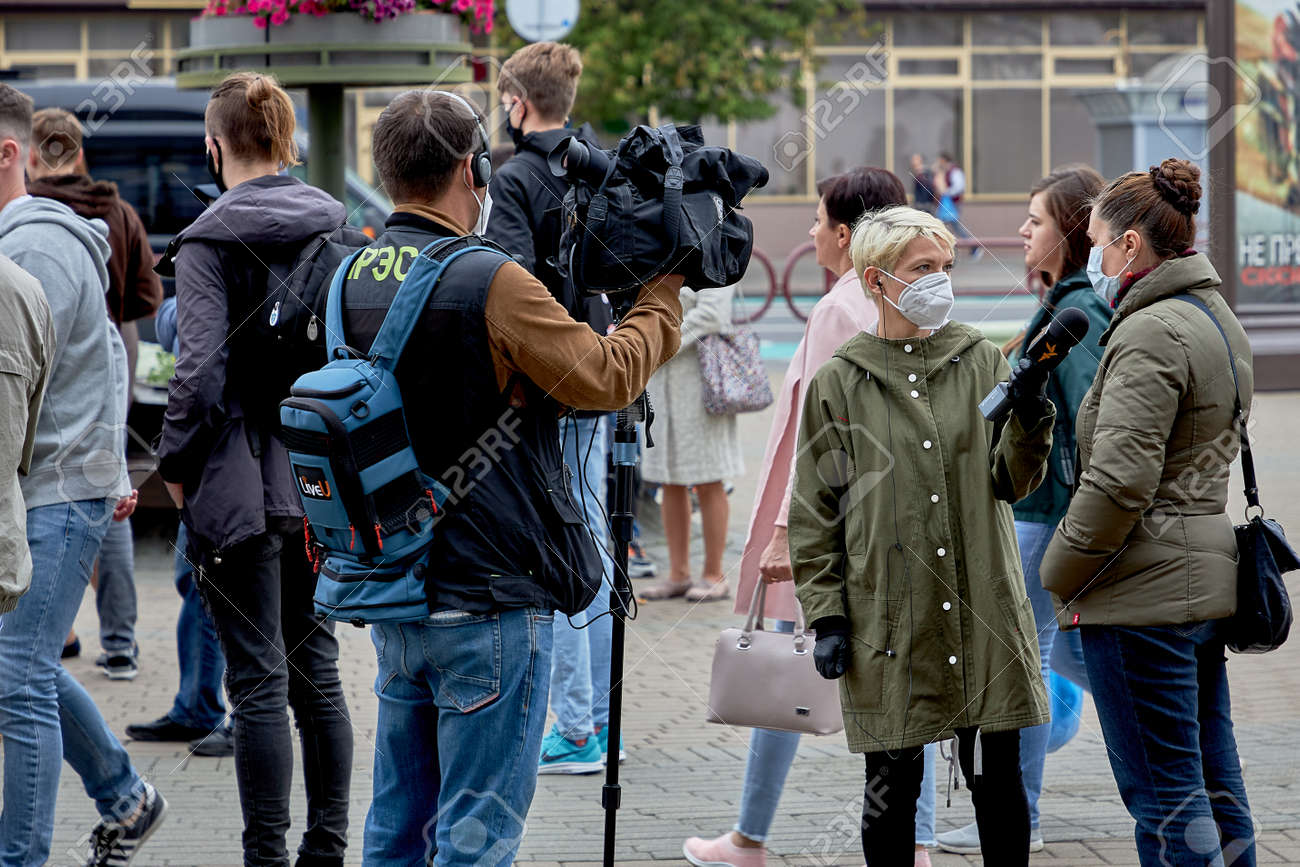 June 14 2020 Minsk Belarus A female reporter with a microphone and a man with a camera interview a masked woman at a protest rally - 151306465