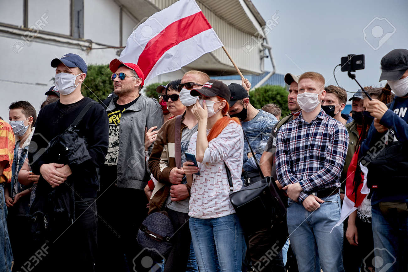 June 7 2020 Minsk Belarus People in medical masks stand at a protest rally.An opposition flag is being raised over people - 151307341